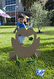 child throwing beanbag through frog cut-out