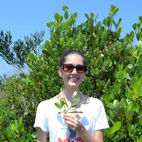 woman smiling holding plant