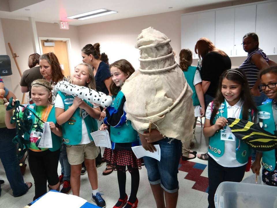 girl scouts holding models of butterfly metamorphosis stages