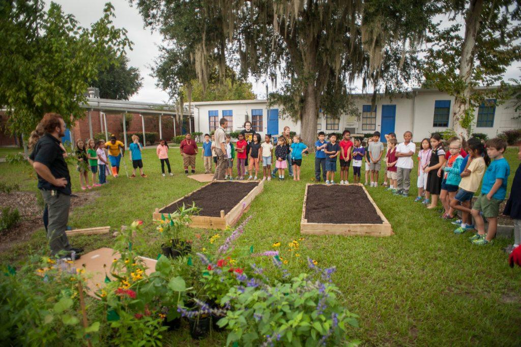 children standing around two freshly tilled garden beds