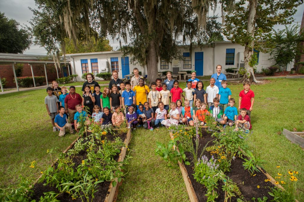 group photo of children with freshly planted butterfly gardens