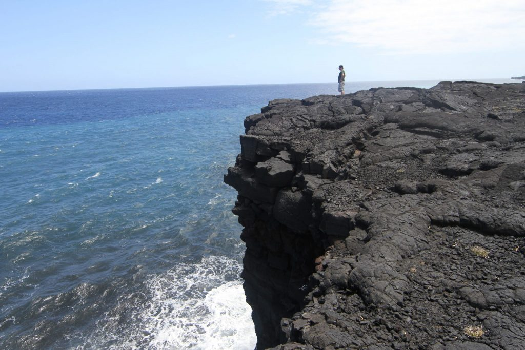 scientist standing near the edge of a rocky outcrop