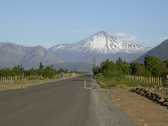 a snowcapped mountain with an empty road leading towards it