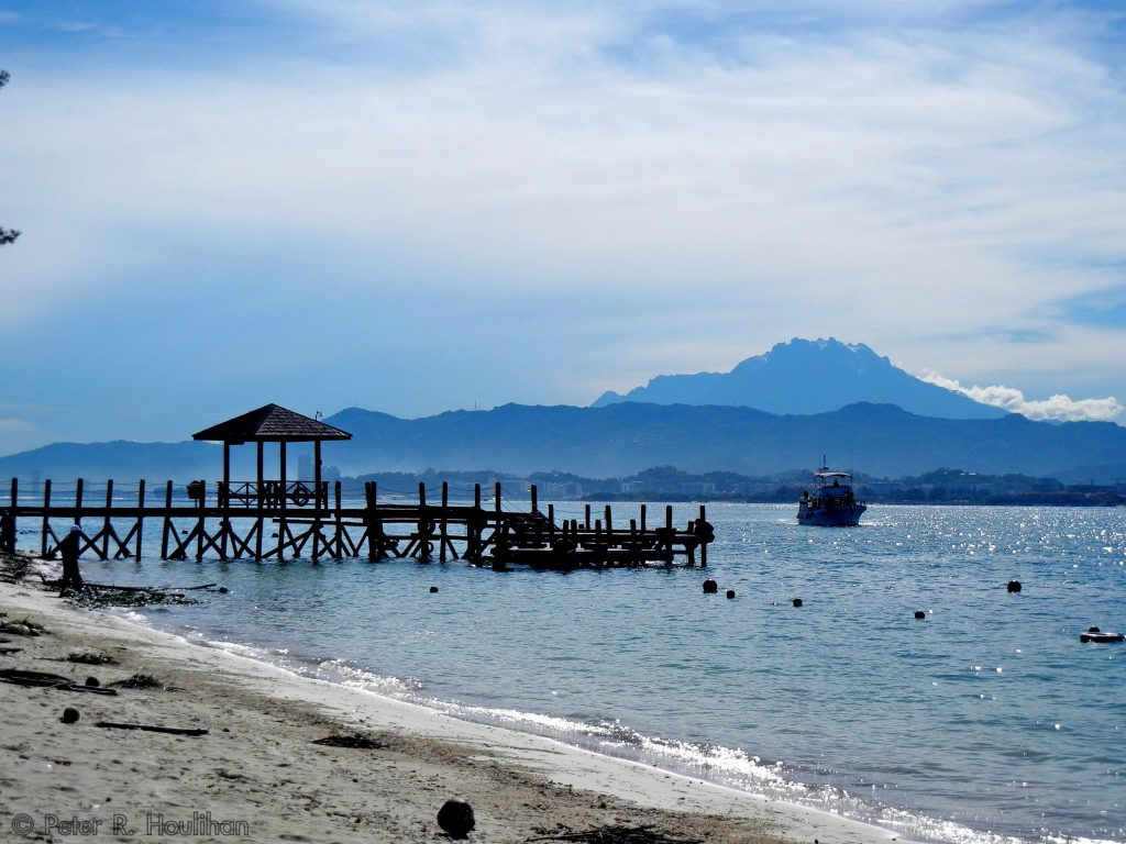 beach in Borneo with a coastal city and mountains in the background
