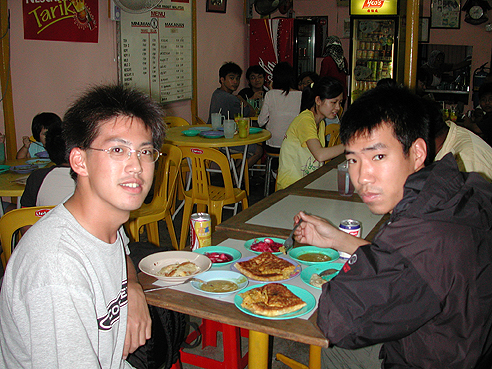 researchers eating a meal at a small Malaysian restaurant
