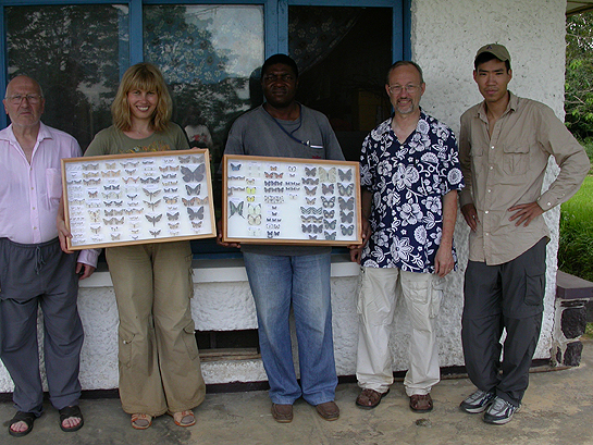 scientists holding two framed collections of moths and butterflies