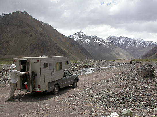 camper truck on an unpaved moutain road with snowcapped mountains in the background