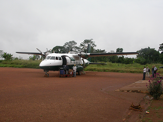 propeller plane parked on a dirt runway