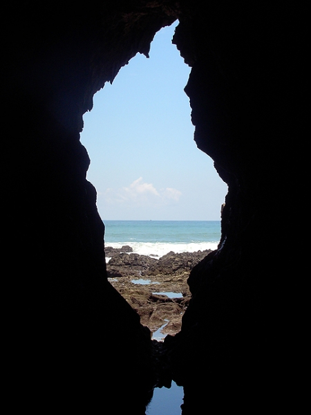 photo of ocean coast taken from the mouth of a cave