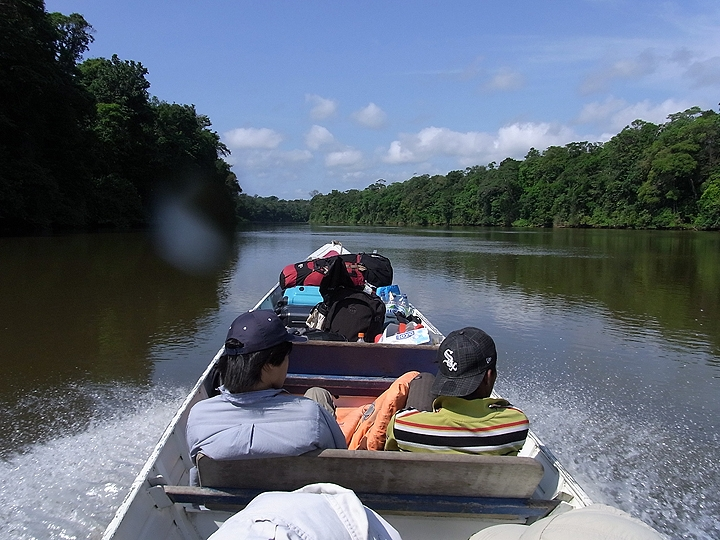 scientists riding in a boat on a river