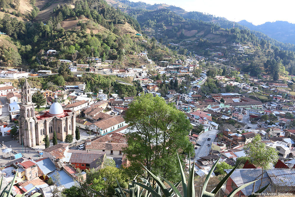 View of the town of Angangueo with many red tile roofs, a tall cathedral, and tree covered hills.
