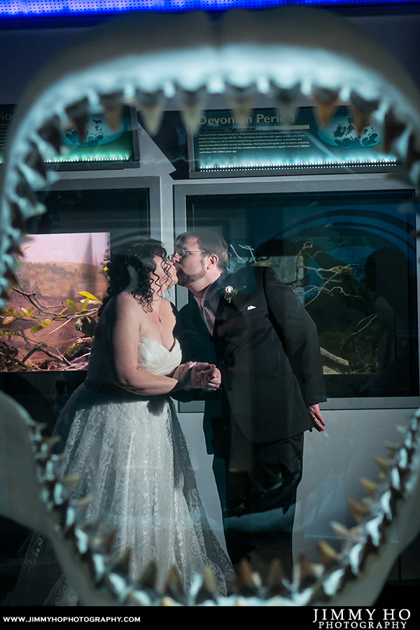 Bride and groom behind fossil shark jaws