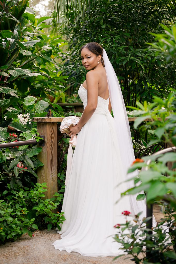bride posing in rainforest with bouquet