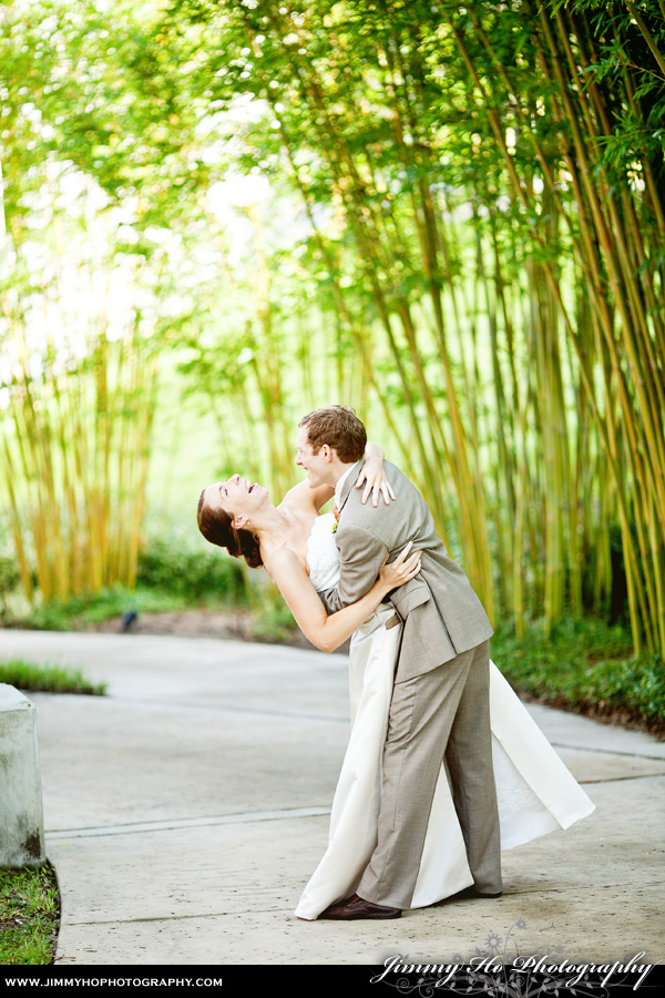 groom dipping bride on walkway with bamboo in background