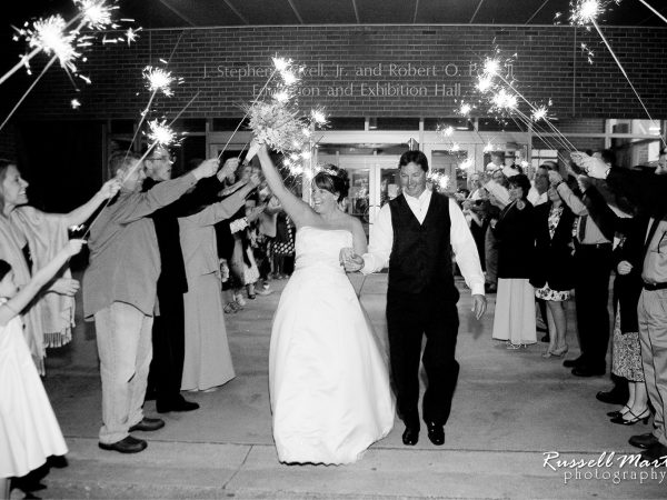 bride and groom exiting musuem in a walkway of sparkers