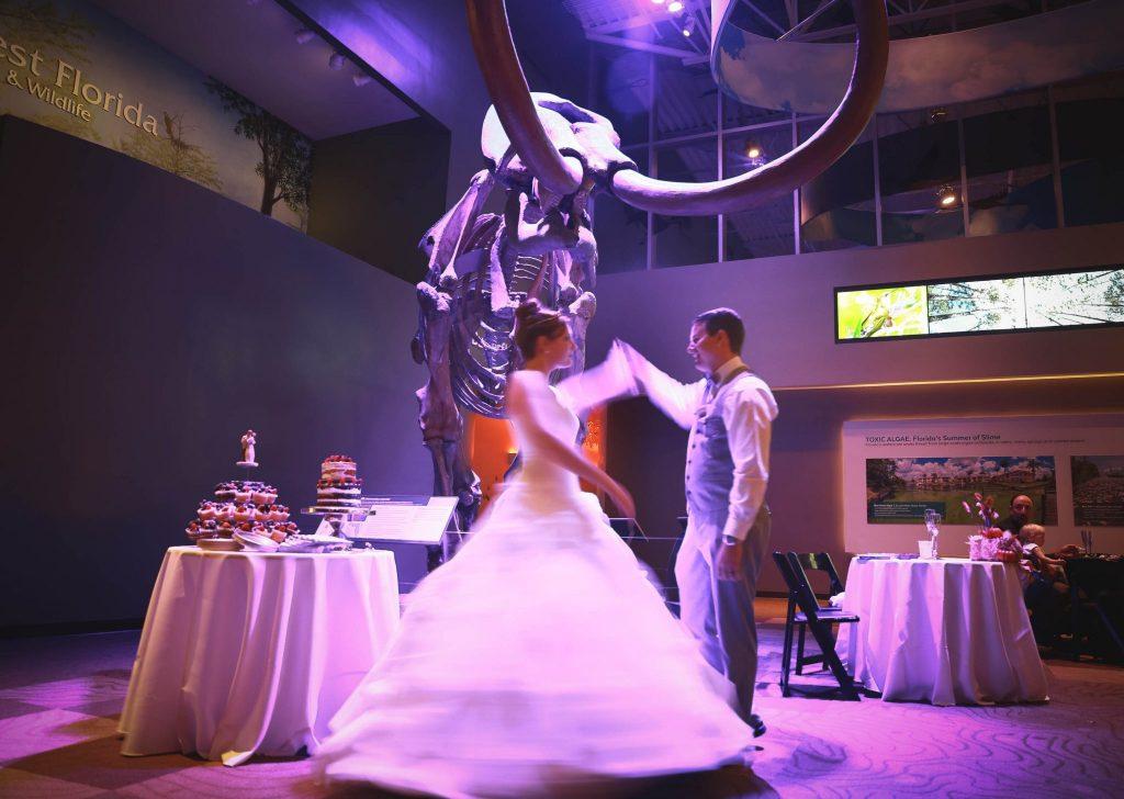 groom spinning bride in front of mammoth (in purple lighting)