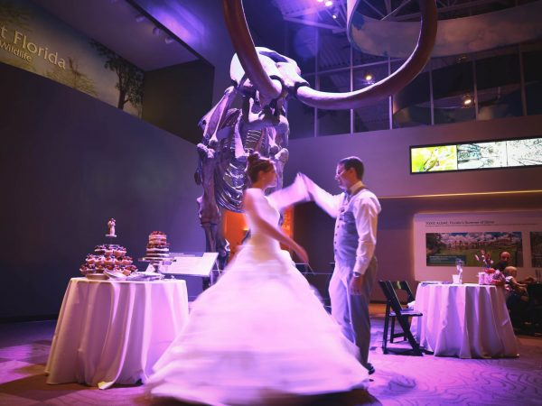 groom spinning bride in front of mammoth (in purple lighting)