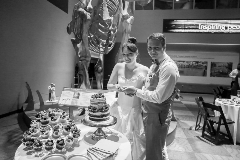 bride and groom cutting cake in front of mammoth skeleton