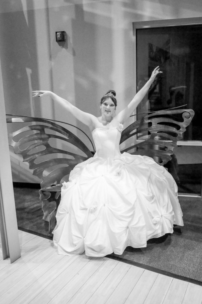 bride sitting with hands in air on butterfly-shaped bench