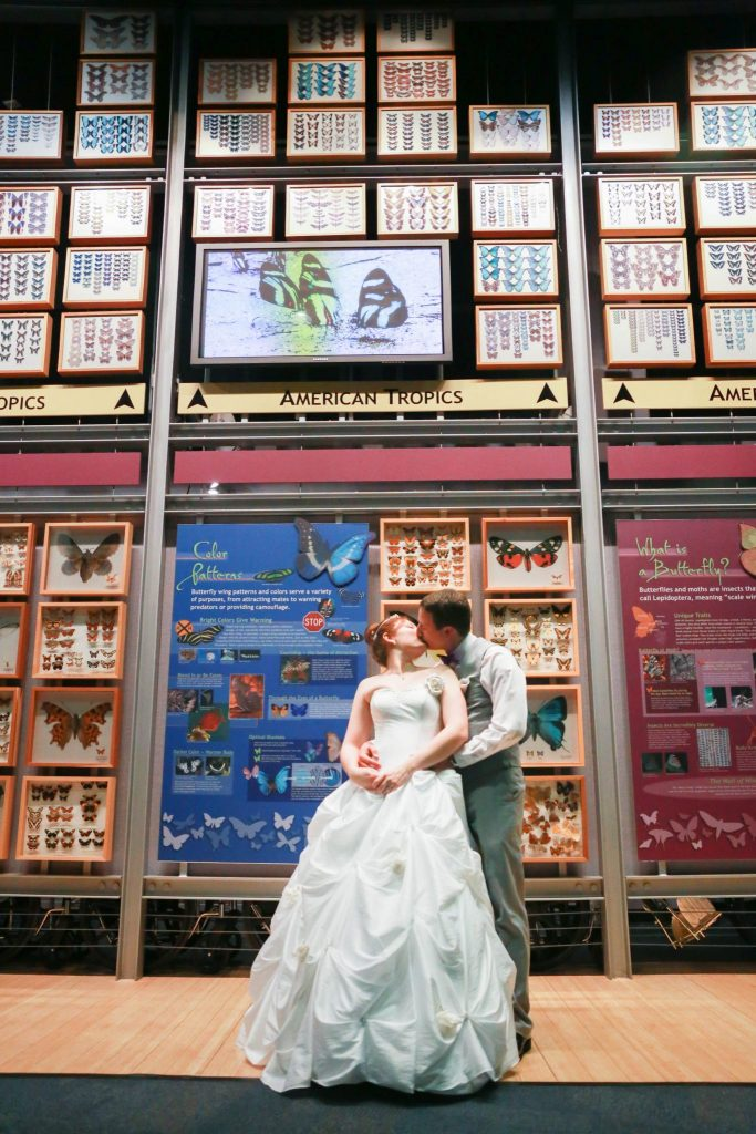 """bride and groom kiss in front of the """"Wall of Wings"""" exhibit"""