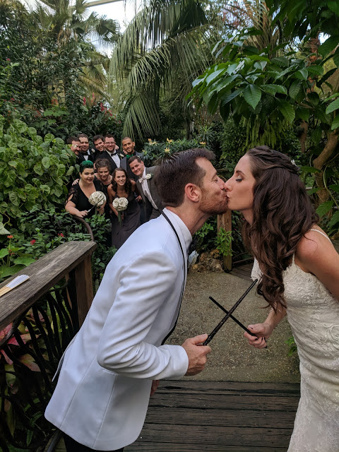 Bride and groom kiss in the Butterfly Rainforest, holding magician's wands as the wedding party looks on.