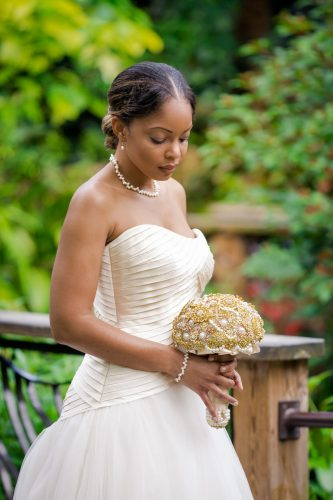 bride in strapless wedding dress holds gold-colored bouquet in rainforest exhibit