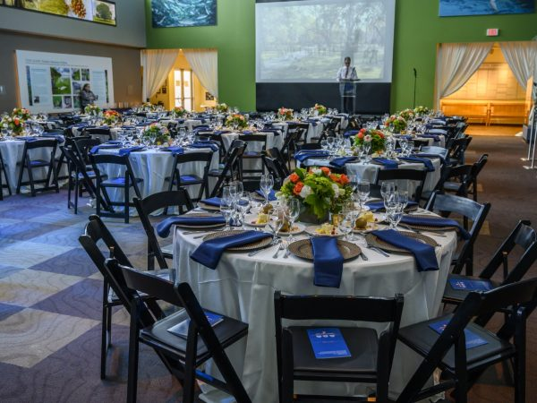 """Seated 60"""" rounds with orange and white floral centerpieces, cream colored linens, and dark blue napkins on bronze-colored chargers. Screen is down and a man is standing at the lectern on a stage in front of the screen."""