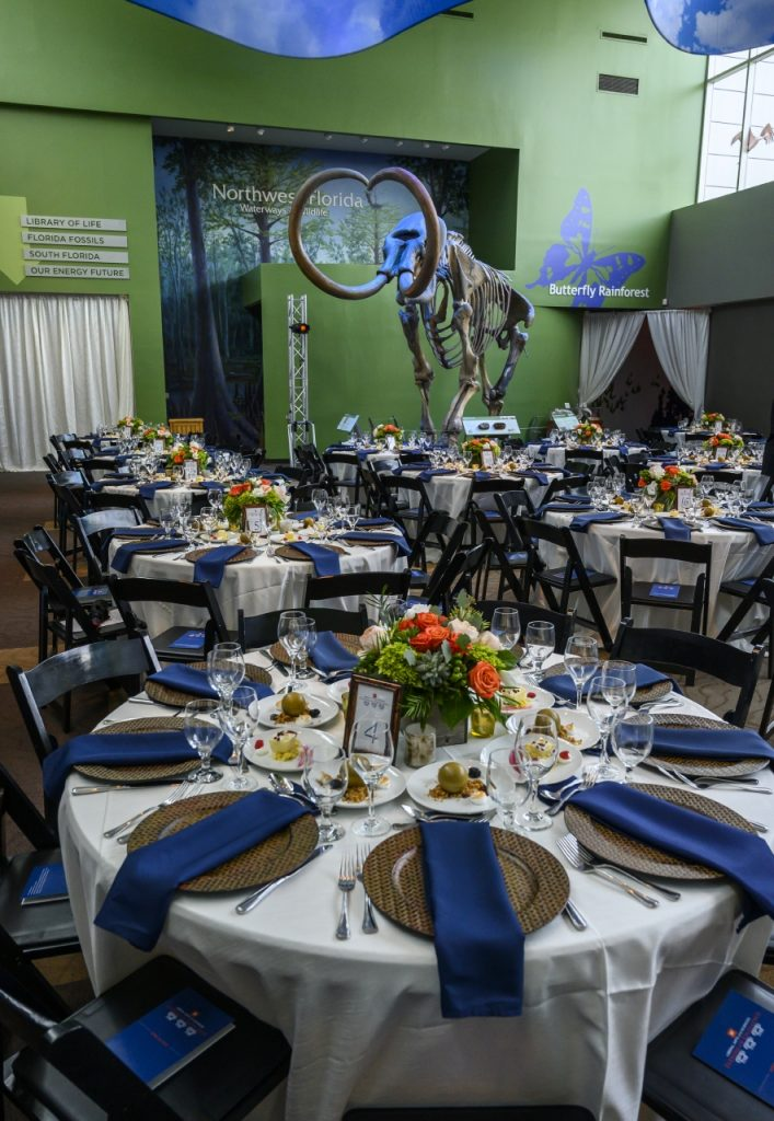 "Seated 60"" rounds with orange and white floral centerpieces, cream colored linens, and dark blue napkins on bronze-colored chargers. Mammoth lit in light blue in background."