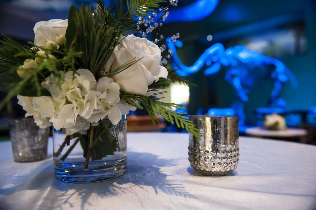 Flowers and candle on tabletop with mammoth lit in blue in background