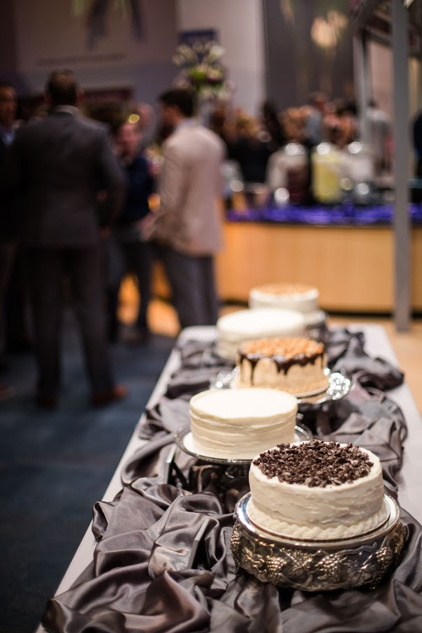 Multiple cakes set up on table with guests in background