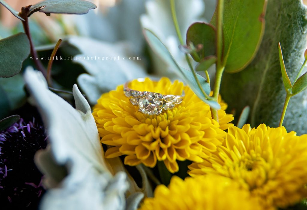 Zoomed-in photo of wedding ring on top of yellow flower in the bouquet.