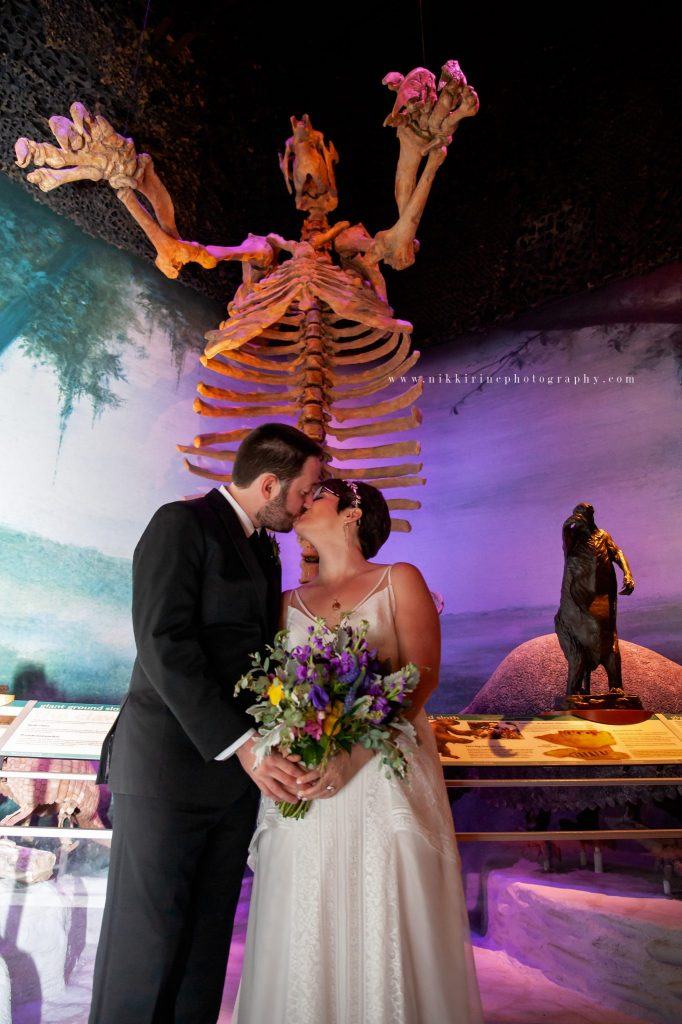 Bride and groom kiss in front of giant sloth skeleton.