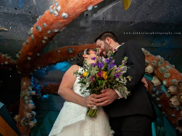Bride and groom kiss in the musuem's underwater room with models of giant sea creatures surrounding them.
