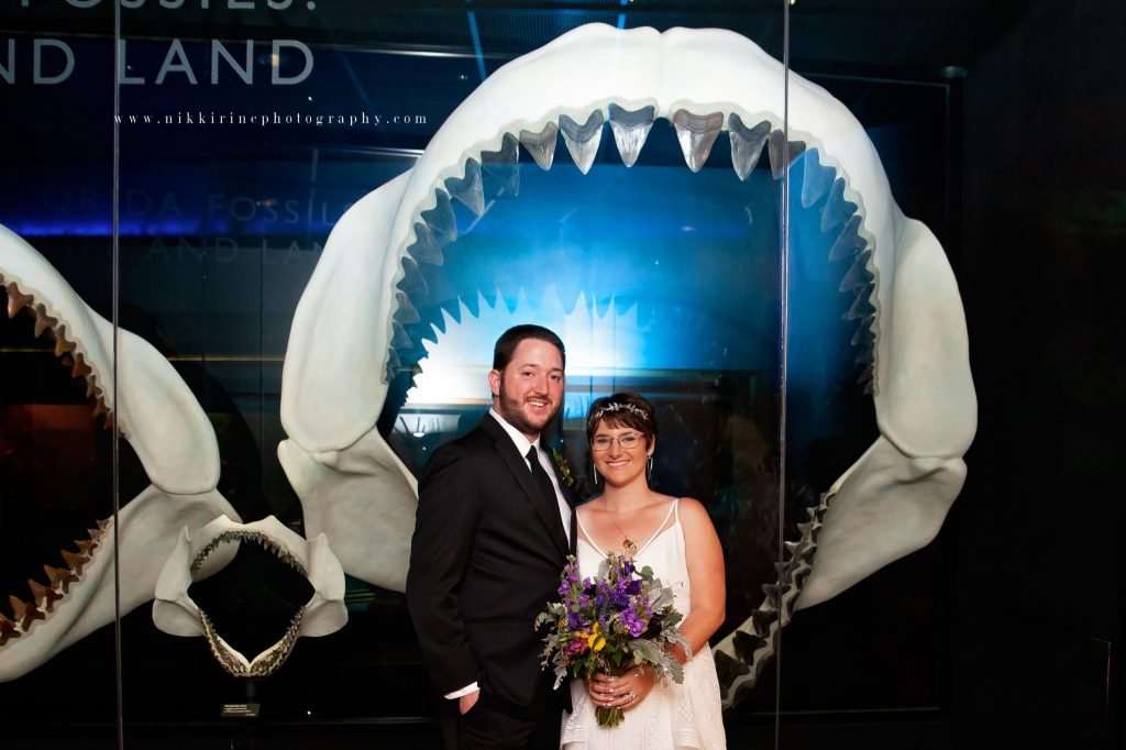Bride and groom pose in front of giant shark jaws.