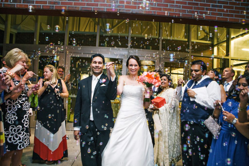 Couple exit museum in a flurry of bubbles blown by their wedding guests.