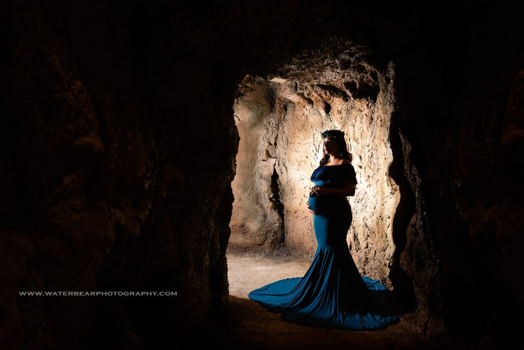 Pregnant woman stand in profile, backlit, in the shadow of the entrance to a cave