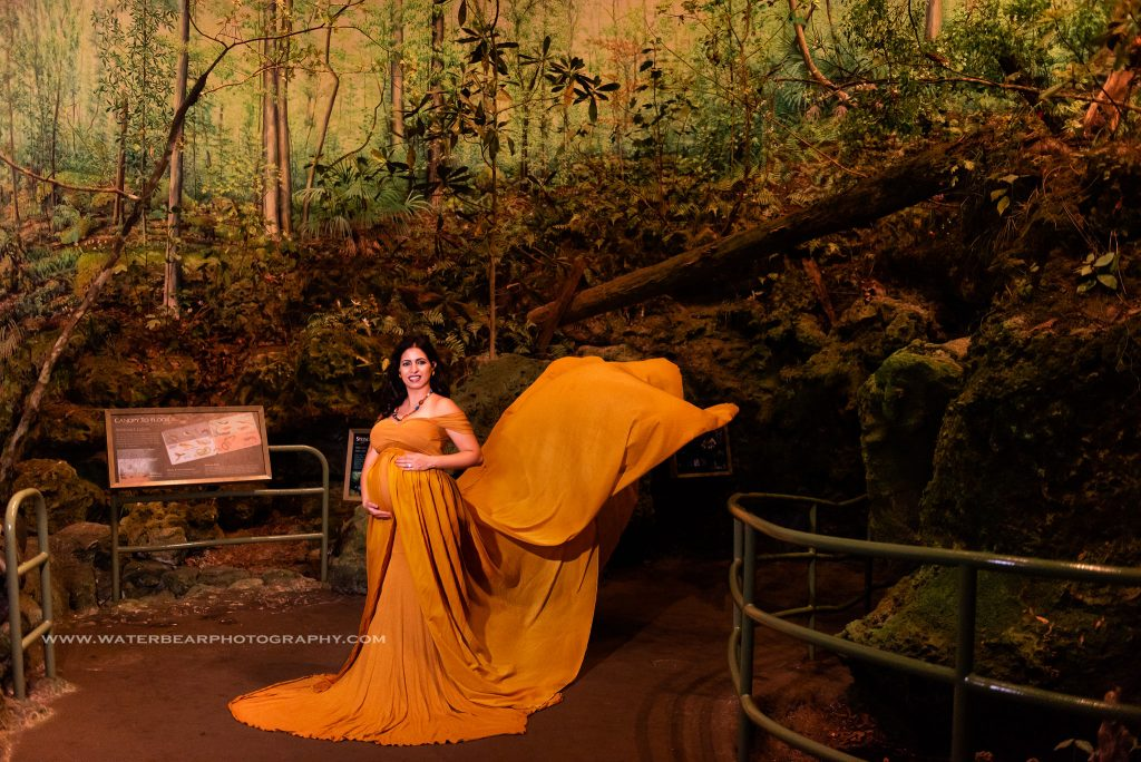 pregnany woman stand in Northwest Florida echibit against a forest backdrop, wearing a mustard colord dress that is fluttering behind her