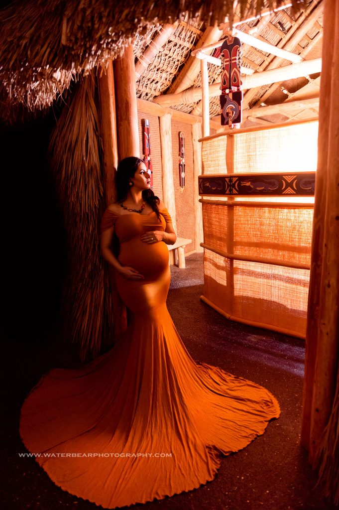 pregnany woman wearing mustard colored dress leans against entrance to Native American hut with the lighting and colors mimicking her dress