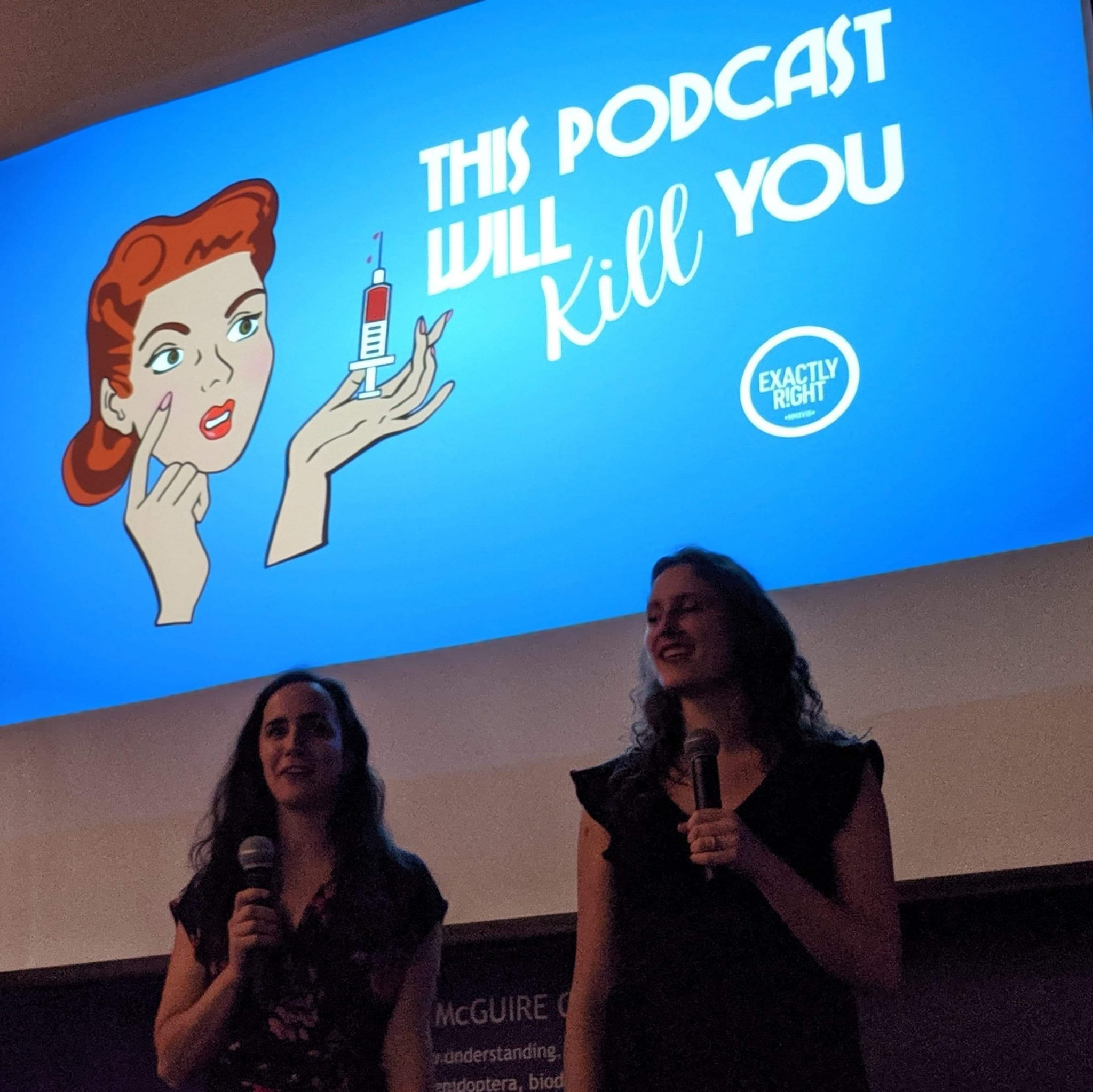 "The Erins sit in front of a screen showing their logo, a woman with red hair in a 50s style holding a needly with the words ""This Podcast Will Kill You"" and the Exactly Right network logo in white on a blue backdrop."