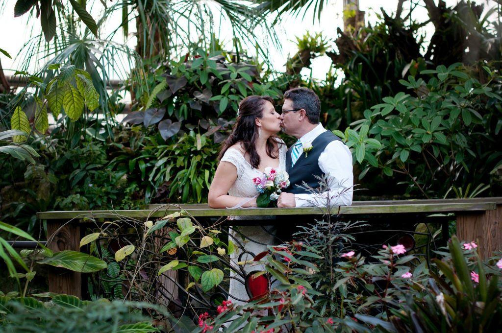 bride and groom lean against bridge railing and kiss in the Rainforest
