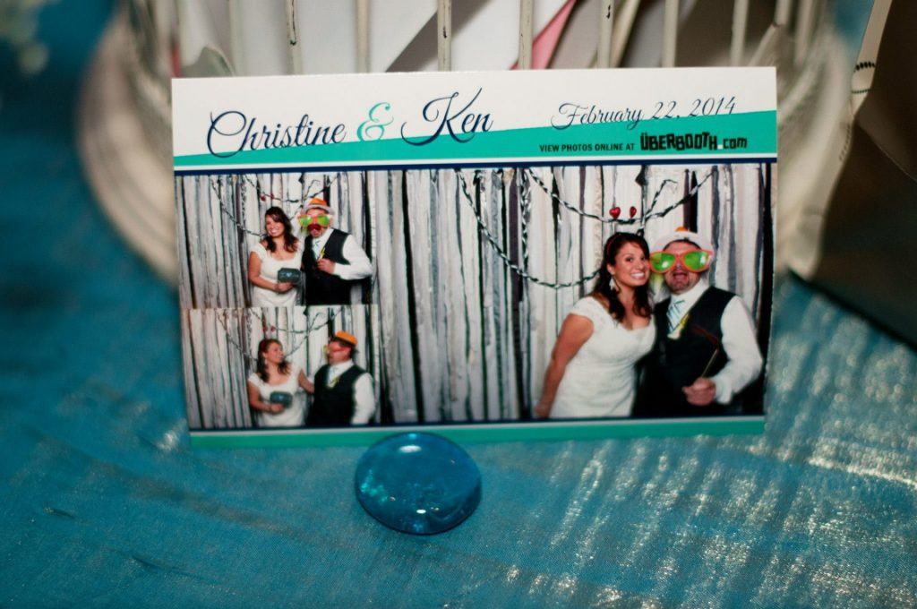 photobooth printout of bride and groom in three different poses wearing hats and masks, sitting on a table with a teal linen