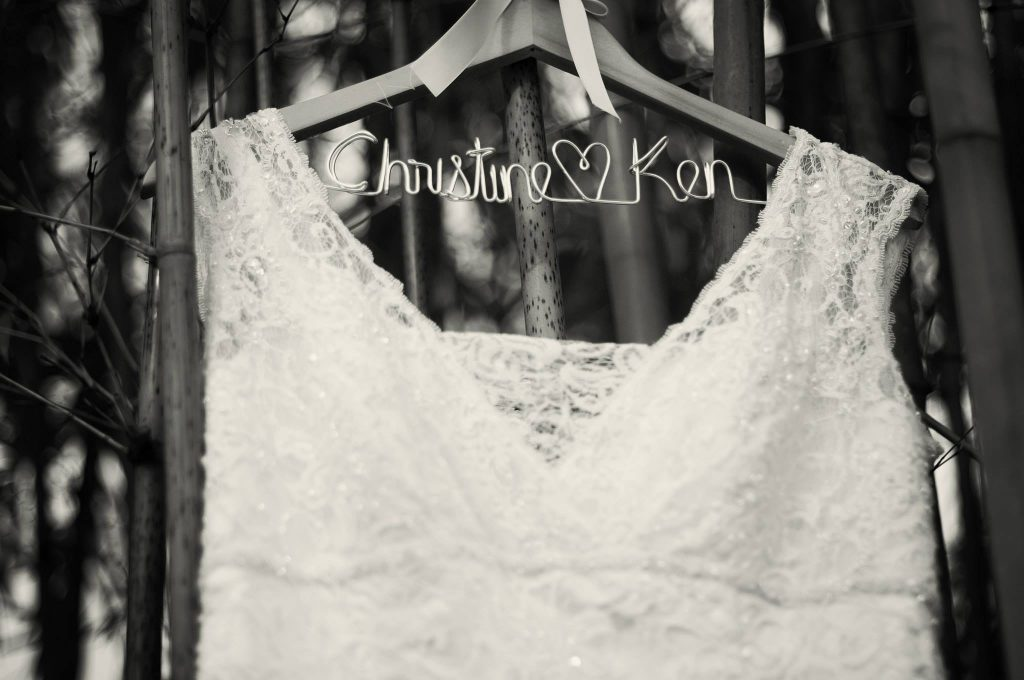"close-up of top of bridal gown, hanging from bamboo on a hanger with the words ""Christine & Ken"" made of metal wiring"