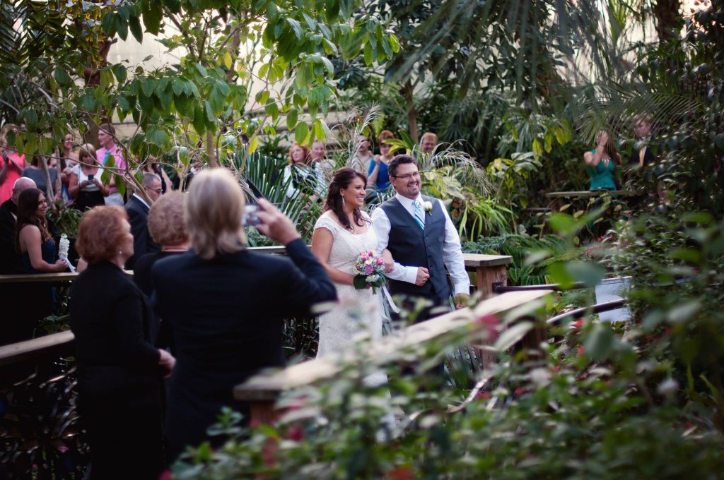 bride and groom smile, surrounded by family and friends, after jsut having completed their ceremony in the butterfly rainforest