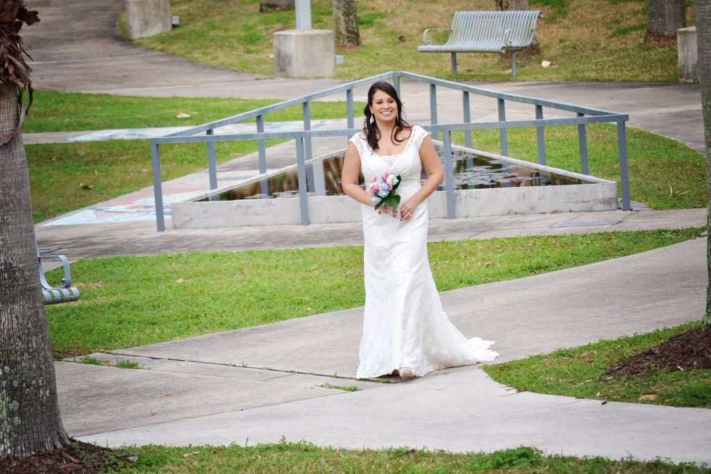 Bride holding bouquet walks along the sidewalk to approach her groom for teh first look.
