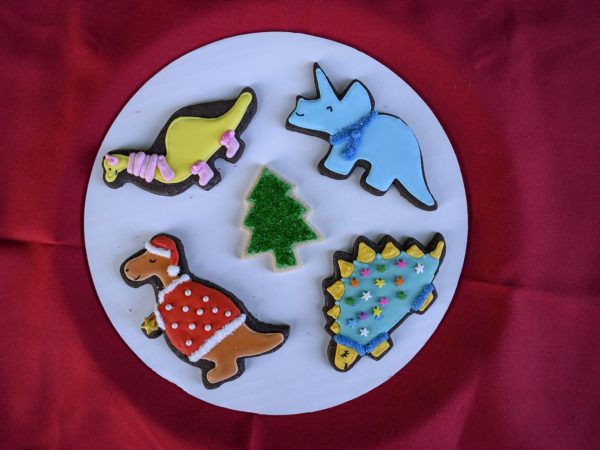 a platter of cookies shaped liked dinosauras wearing winter hats, sarves, etc and a Christmas tree