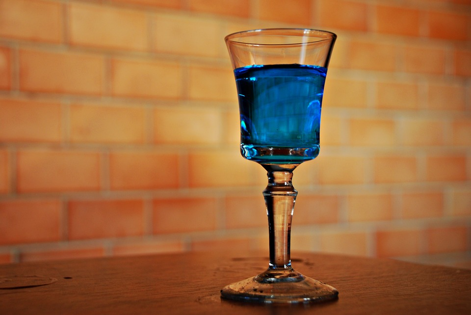 blue drink in clear wine glass against golden-colored backdrop
