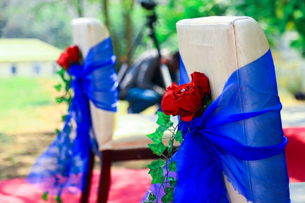 cream-colored cushioned event chairs with blue sashes and red flowers tucked into the knot