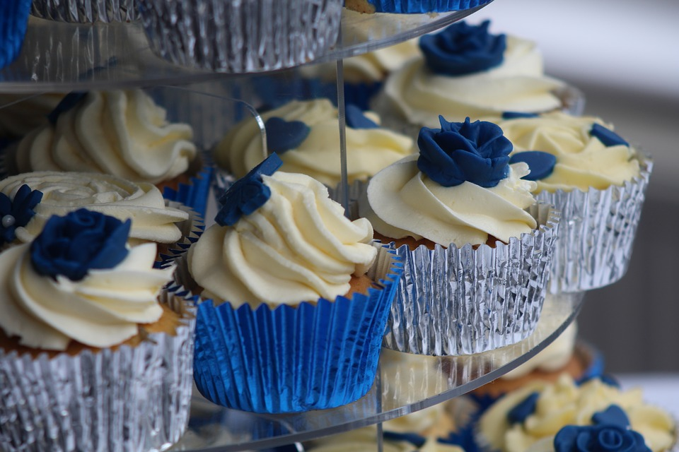 vanilla cupcakes with white forsting and blue tips, in silver and blue foil wrappers