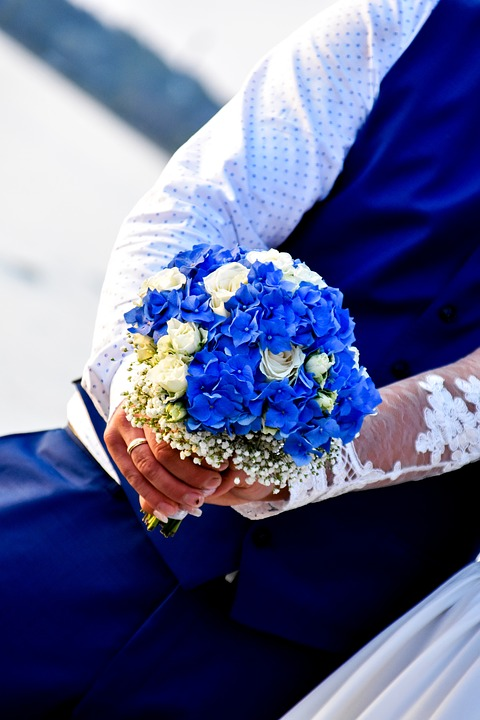 a couples arms holding a bouquet containing blue and white flowers