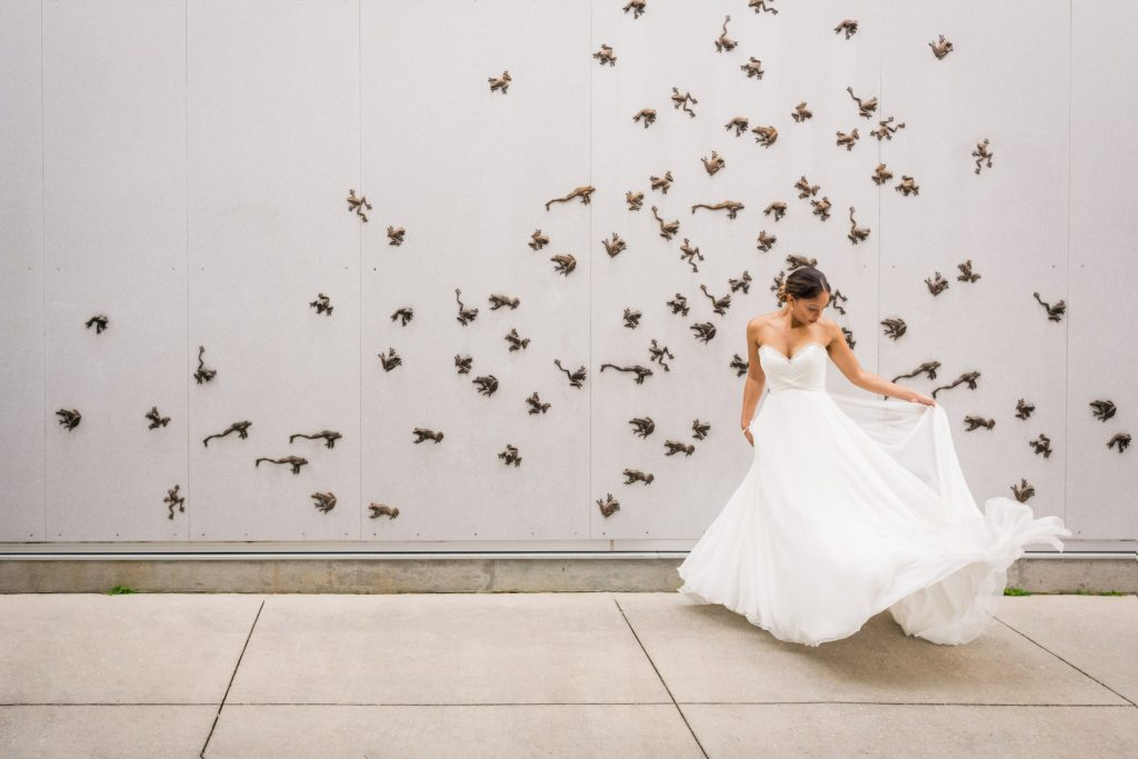 Bride stands in flowing strapless white wedding dress in front of a wall covered in bronze frogs leaping around.
